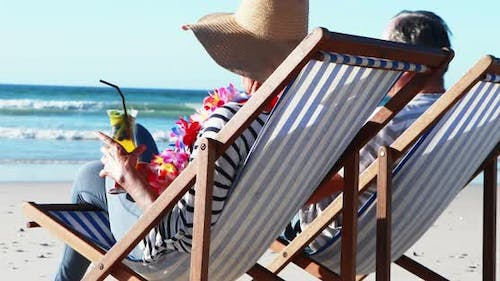 Senior couple sitting on sunlounger and having cocktail at beach