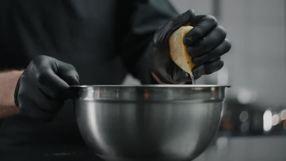 Thumbnail for Chef in Black Gloves Squeezes Lemon To the Metal Bowl in Slow Motion, Lemon Sprinkles, Raw Natural