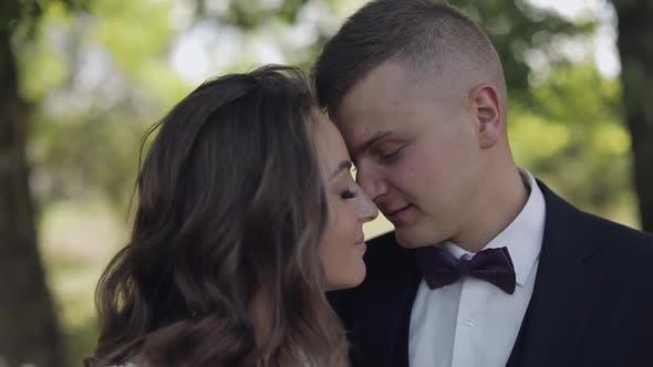 Thumbnail for Groom with Bride Making a Kiss in the Park. Wedding Couple. Happy Newlyweds