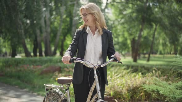 Portrait of Smiling Blond Middle Aged Woman in Suit Sitting on Bike and Leaving