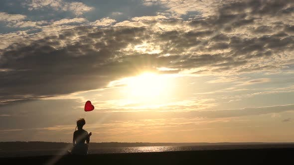 Cover Image for Lonely Woman with Heart Balloon Watching Sunset