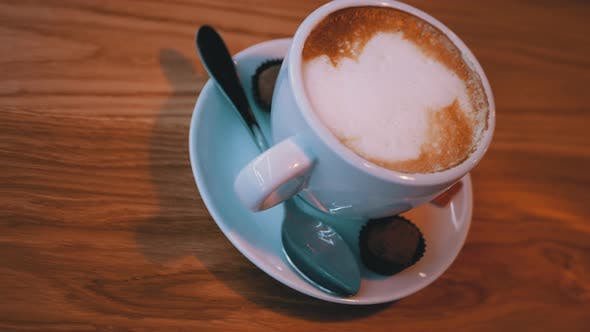 Thumbnail for Tasse Cappuccino mit weißem Schaum auf dem Holztisch im Restaurant
