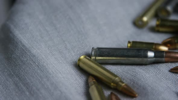 Cinematic rotating shot of bullets on a fabric surface - BULLETS 096