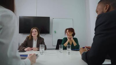 Business Woman Talking to Colleagues at Meeting