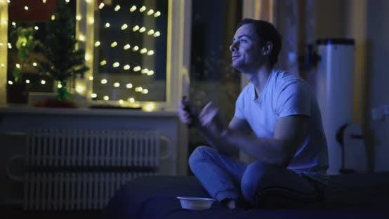 Joyful Man Watch TV and Dancing at Home