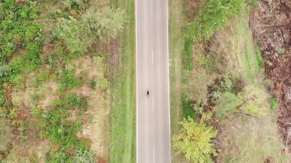 Thumbnail for Cyclist rides bike on empty car road countryside. Athlete is spinning pedals on aero bicycle outdoor