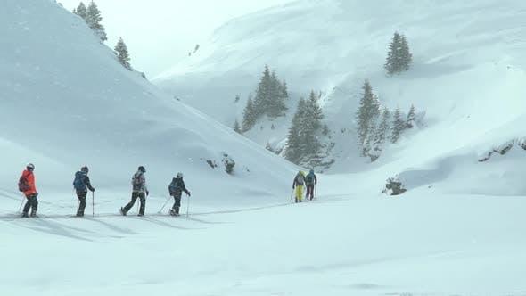 Gruppe von Kindern, die Skitouren mit einem Führungstrainer machen. Skitouren in den Bergen