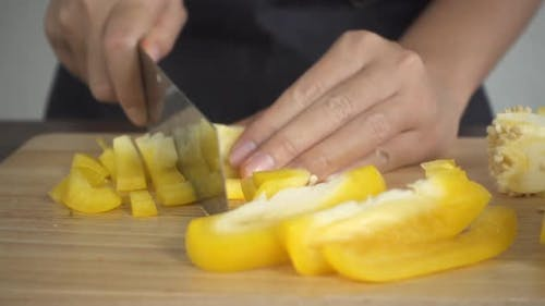woman making healthy food and chopping bell pepper on cutting board in the kitchen.