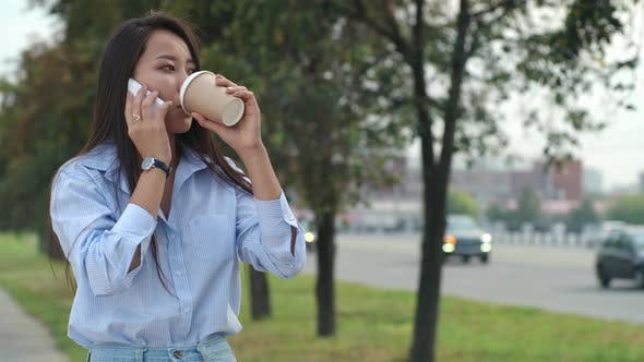 Thumbnail for Woman Talking on Cell Phone and Drinking Coffee on Street