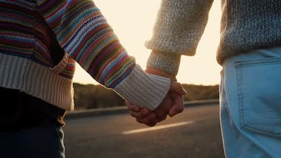 Adult mature couple walking holding hands with love and romance on a street with sunset