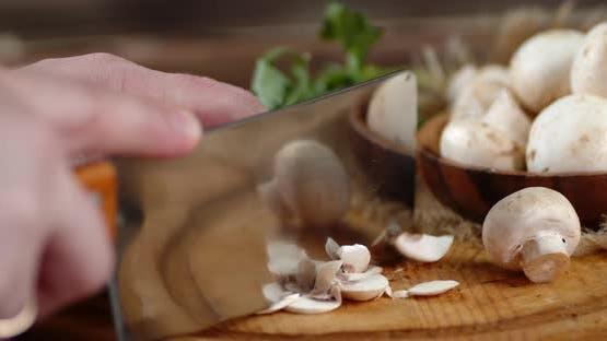 Man's Hand zerkleinerte frische Pilze mit einem großen Messer