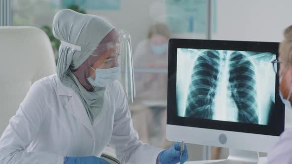 Ärztin in Hijab erklärt männlichen Patienten Röntgen