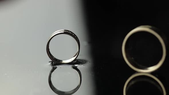Thumbnail for Wedding Rings on Black, White Water Surface. Groom Ring Rolling To Bride's Ring