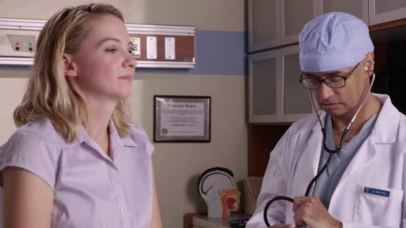 Thumbnail for Doctor checking woman's heart with stethoscope