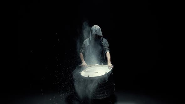 Thumbnail for Hooded Man Beats Drum with Flour