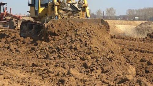 Bulldozer Shifts Earthen Pile