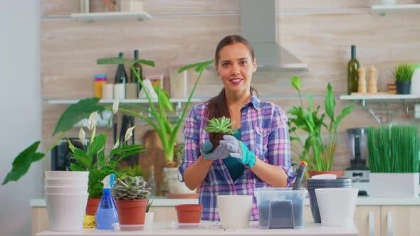 Portrait of Happy Woman Holding Plant