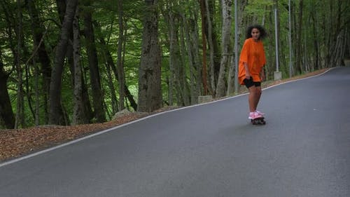 Sporty Brunette Skateboarding Down the Parkway