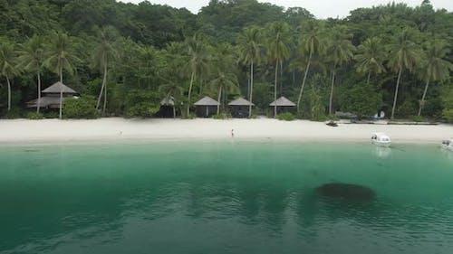 Beautiful Girl Walking On Ocean Beach With Huts Among Palm Trees In Triton Bay, Raja Ampat
