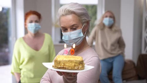 Portrait of Caucasian Woman in Coronavirus Face Mask Posing with Cake and 50 Years Candles on It