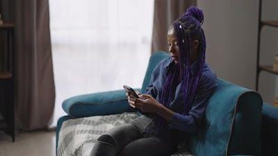 Black Teen Girl is Reading Ebook in Smartphone or Looking for Information in Internet Afroamerican
