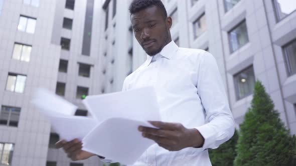 Thumbnail for Handsome African American Man in White Shirt Looking Through Papers Standing on the City Street