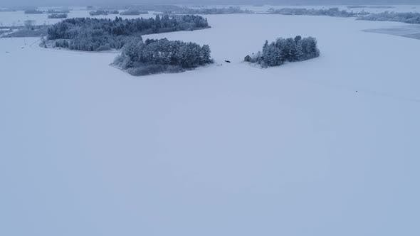 Thumbnail for Aerial view of snowy forests and farmlands in Estonia.