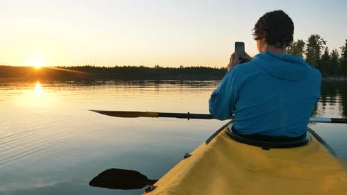 Man Takes a Photo of Sunset on Smartphone on Lake on Kayak with Paddle, Self-isolation Outdoor