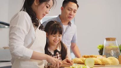 Asian happy family making food preparation in kitchen room at house together. Family relationship.