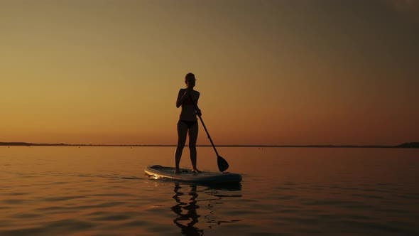 Siluet of Woman Standing on SUP Board and Paddling Through Shining Water Surface