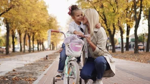 Little Girl Umarmt und küsst Ihre Mutter beim Gehen im Park