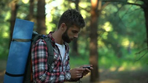 Male Lost in Forest Using Compass to Navigate