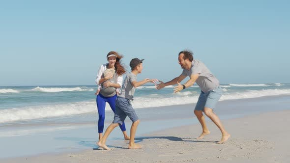 Young Happy Family Enjoy Vacation on Beach Ocean