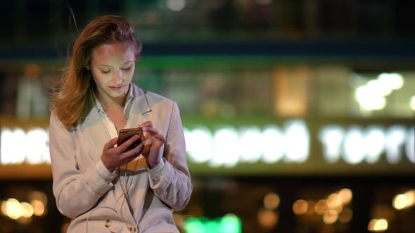 Cover Image for Beautiful woman using her phone late at night when lights