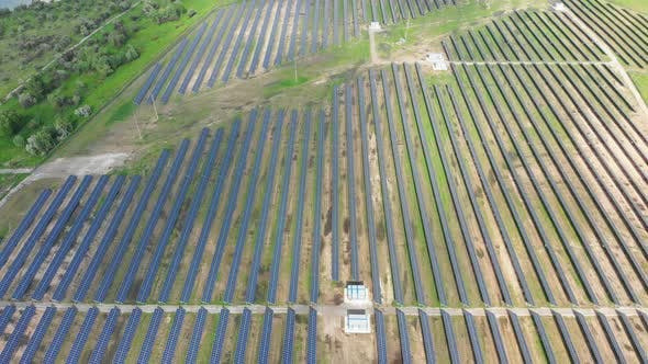 Cover Image for Aerial Top View on Solar Power Station in Green Field on Sunny Day. Solar Farm
