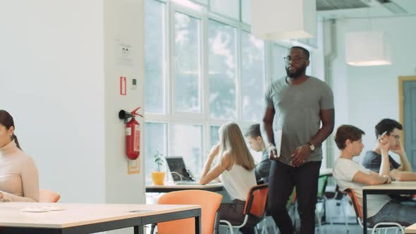 Thumbnail for African Man Coming in Coworking Space. Closeup Serious Man Opening Laptop