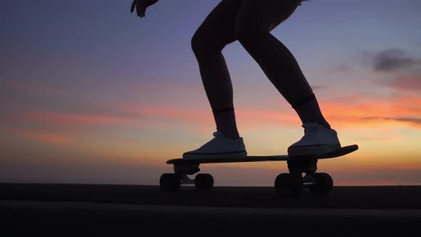 Thumbnail for Beautiful Girl Rides a Skateboard on the Road Against the Sunset Sky. Close Up