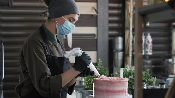Precautions, Female Chef in Medical Mask and Gloves Decorated Homemade Cream Cake Is Pouring Cream