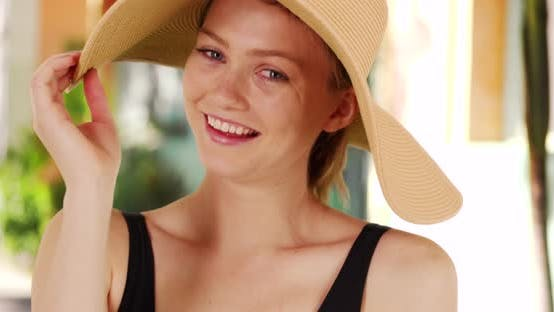 Cover Image for Woman with sunhat smiling laughing and playing with hat while looking at camera