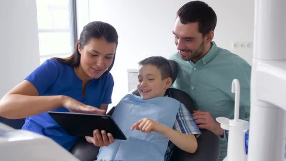 Cover Image for Dentist Showing Tablet Pc To Patient at Clinic 39