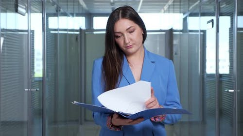 Concentrated Brunette Businesswoman Looks Through Reports