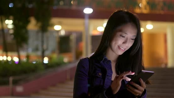 Cover Image for Woman look at smart phone in city at night