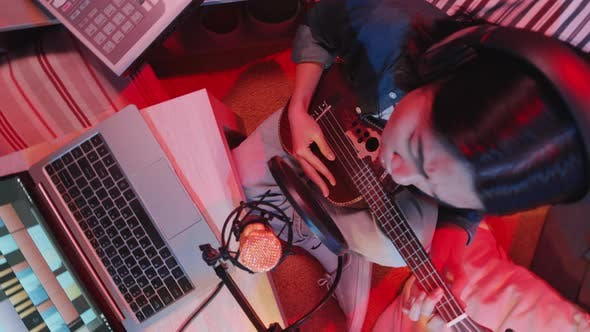 Top Down Shot of Woman Recording Guitar Song in Home Studio