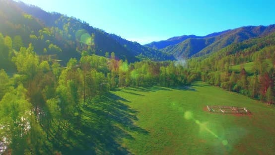Thumbnail for Mid Air Flight Over Fresh Mountain River and Meadow at Sunny Summer Morning. Rural Dirt Road Below