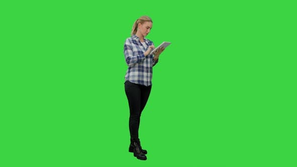Thumbnail for Young Woman Standing on Green Background with Digital Tablet on a Green Screen