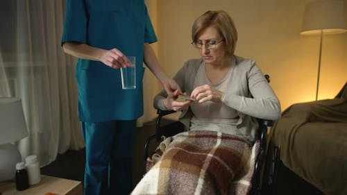 Female Carer Giving Pills to Hospital Patient in Wheelchair, Rehabilitation