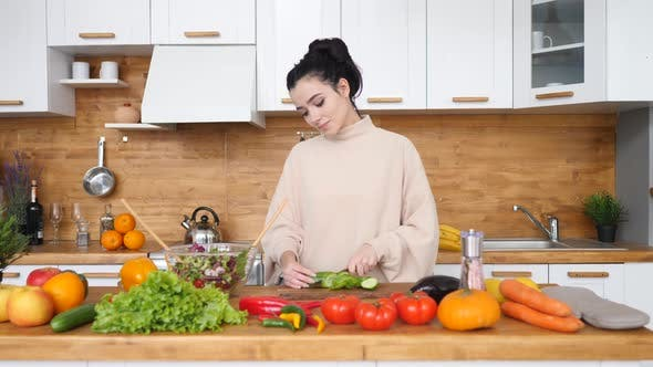 Young Woman Cooking In The Kitchen. Healthy Food - Vegetable Salad. Diet. Dieting Concept. Healthy