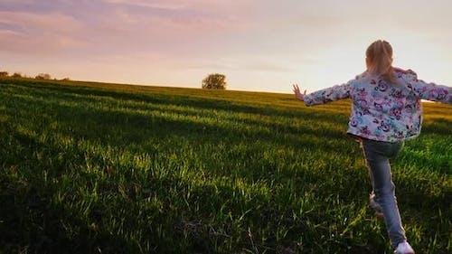 A Little Girl Runs Across the Field Like an Airplane