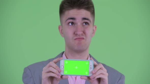 Thumbnail for Face of Happy Young Businessman Thinking While Showing Phone