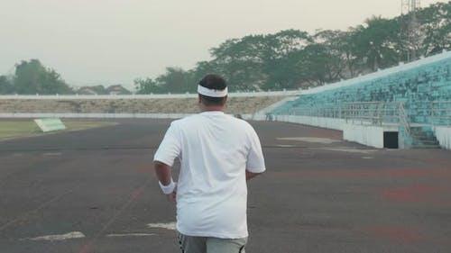 Asian Fat Man Jogging At Stadium